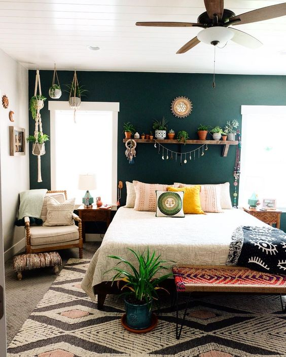 a boho bedroom with a dark green accent wall, a bed, a woven bright bench, a neutral chair, a shelf with plants and more hanging planters