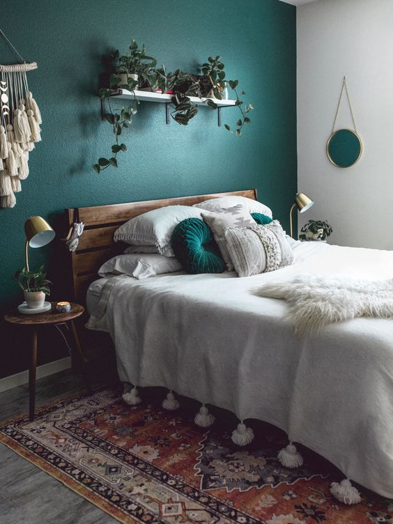 a boho bedroom with an emerald accent wall, a stained bed with neutral bedding, a shelf with potted plants, stained nightstands, a boho rug