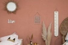 a boho kid bedorom with a pink accent wall, a wooden bed, nightstand, a peacock chair, pampas grass, some pretty decor and neutral textiles