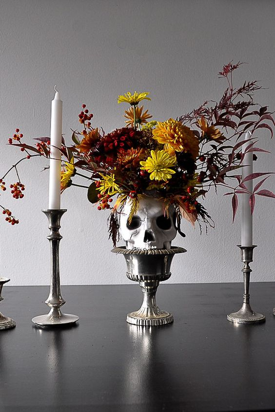 a bold Halloween centerpiece of a bowl holding a skull with super bright blooms, candlesticks and tall and thin candleholders
