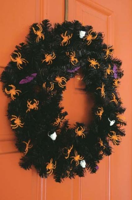 a bold Halloween wreath of black faux evergreens, orange spiders and purple bats plus skulls is very easy to DIY