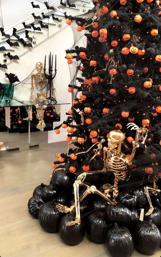 a bold and chic Halloween styled space with a Halloween tree with pumpkin lights, black pumpkins and a gilded skeleton is a fun idea