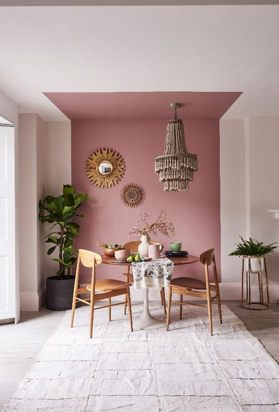 a bold dining space with a dusty pink accent wall, a wooden table and chairs, a beaded chandelier, sunburst mirrors, potted plants and a rug
