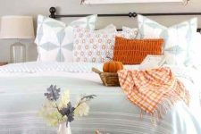 a bold farmhouse bedroom with greige walls, a forged bed with blue and orange printed bedding, a forged chandelier and a grey bench with pumpkins and leaves