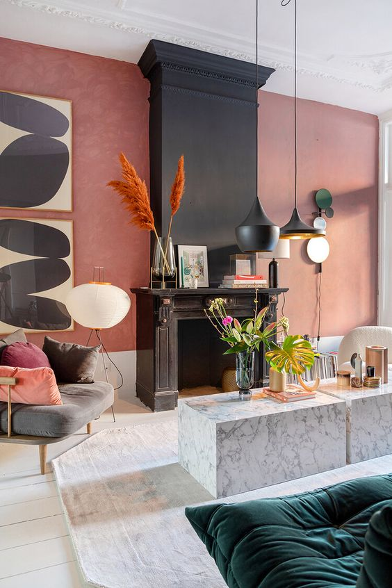 a bold living room with a pink accent wall, a black fireplace, black pendant lamps, a duo of marble tables, various kinds of furniture