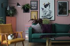 a bold living room with a pink planked wall, a green sofa, a gallery wall, a mustard chair, a zebra rug, potted plants and black sconces
