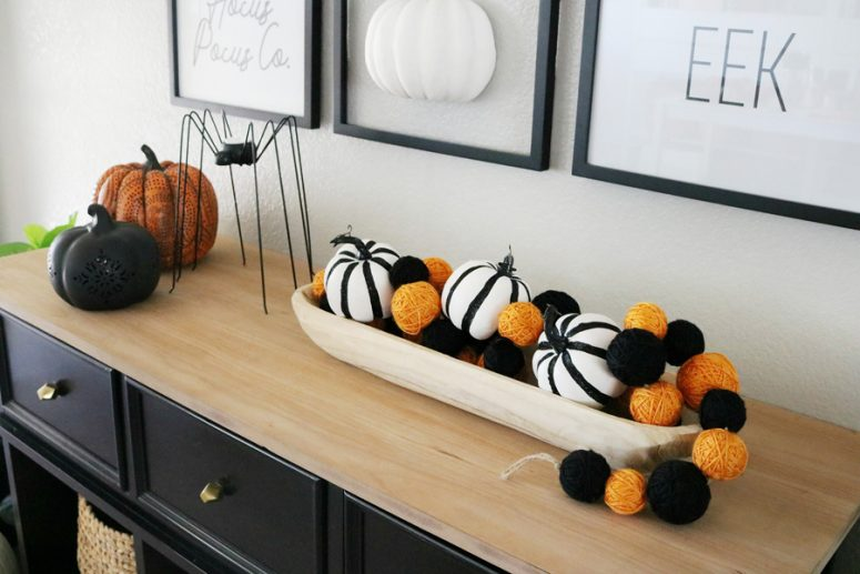a bowl with black and white pumpkins and orange and black yarn balls, faux pumpkins and a spider candle holder