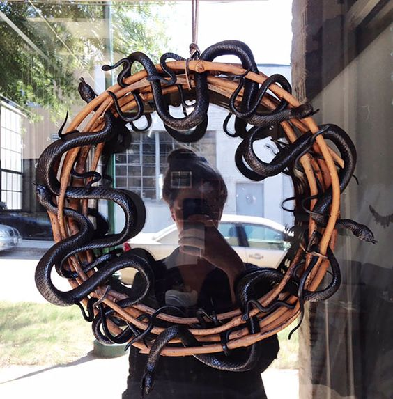 a branch wreath interwoven with black snakes is a simple and timeless idea for Halloween home decorating