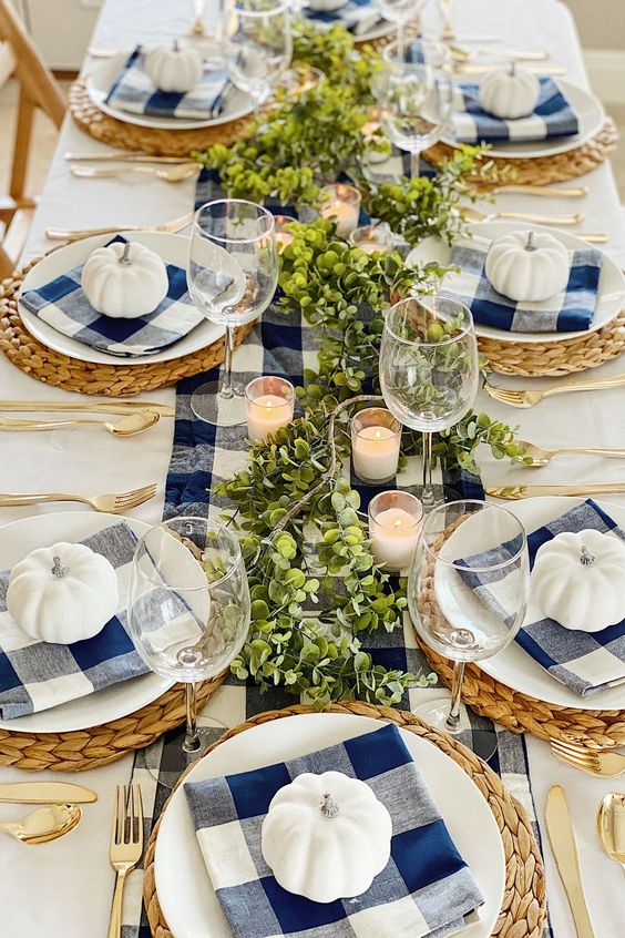 a bright Thanksgiving table setting with a navy plaid runner and napkins, white pumpkins, greenery, candles and woven placemats