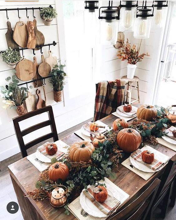 a bright Thanksgiving tablescape with a greenery and pumpkin runner, striped napkins and neutral placemats, a copper kettle