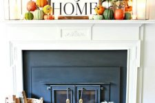 a bright and cool fall rustic mantel with lots of colorful pumpkins, fall leaf branches and candle lanterns plus a sign on top