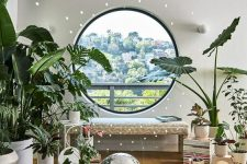 a bright and cool space with a round window with a view of the city, a bench, lots of potted plants and books and a disco ball