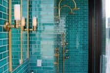 a bright bathroom with turquoise skinny tiles, a pretty black and white floor, a double sink and brass fixtures plus a mirror in a brass frame