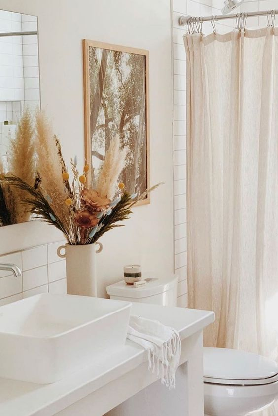 a bright fall arrangement of pampas grass, dried blooms and billy balls in a neutral vase will easily bring a cozy fall feel to your space