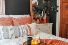 a bright fall bedroom with creamy and white furniture, orange blankets and pillows, a mirror in an orange frame and orange trees and fall scented candles