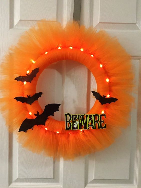 a bright lit up orange tulle Halloween wreath with black bats and letters can be DIYed easily and looks very pretty