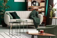 a bright living room with an emerald accent wall, a creamy loveseat, a green chair, mini coffee tables, a bookcase and potted plants