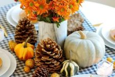 a bright rustic Thanksgiving tablescape with a plaid runner, gourds and pinecones, bold blooms, berries and neutral pumpkins is fresh