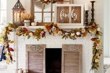 a bright rustic fall mantel with a reclaimed sign, bright leaves and pumpkins, candle lanterns, wooden candleholders with pillar candles and shutters