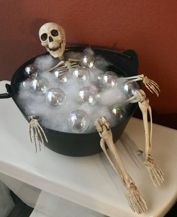 a bucket with fluffs, Christmas ornaments and a skeleton is a creative indoor Halloween decoration you can easily make