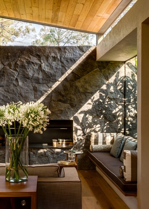 a cabin living room with a stone accent wall, chic furniture, a large window and some clerestory ones for more light