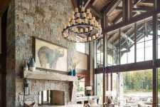 a cabin living room with a tall ceiling with wooden beams, a large fireplace clad with stone, neutral seating furniture and a chandelier