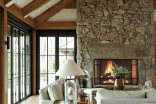 a cabin living room with rich-stained wooden beams, a fireplace clad with stone, neutral seating furniture, a small side table and a lamp