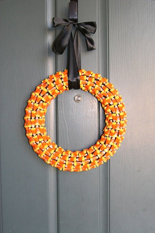 a candy corn Hallowee wreath with a black ribbon bow is a fresh and pretty idea for any styling and decorating