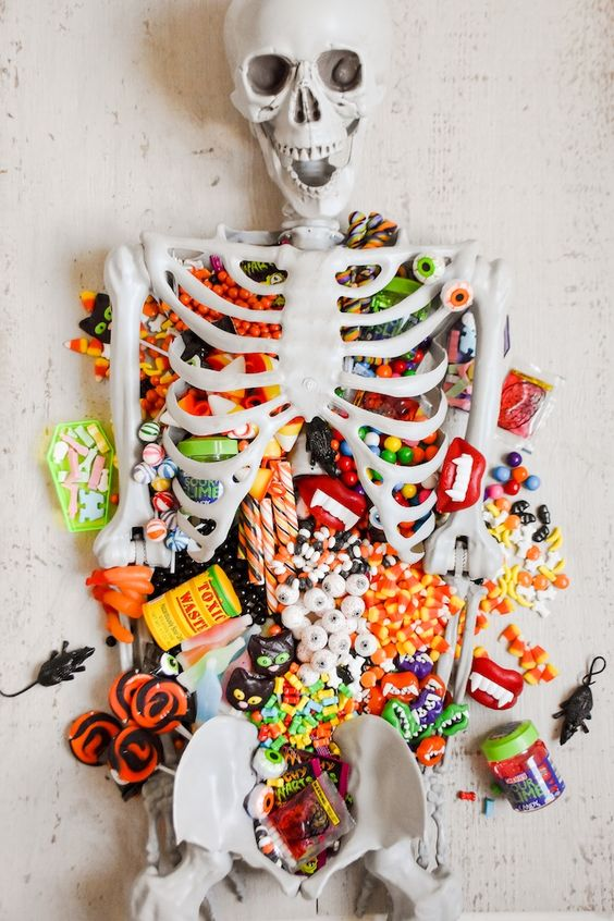 a candy table styled with a skeleton is a perfect solution for Halloween, you can offer sweets to your guests this way