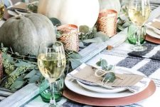 a casual rustic Thanksgiving table with a striped tablecloth, heirloom pumpkins and eucalyptus, green glasses and copper chargers