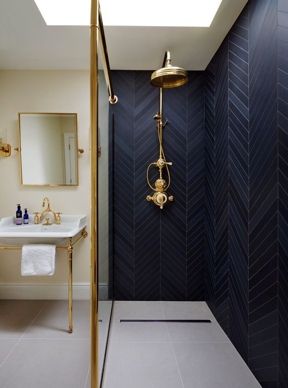 a catchy bathroom with neutral walls, a shower space clad with black and grey chevron tiles, brass and gold fixtures is super chic and shiny