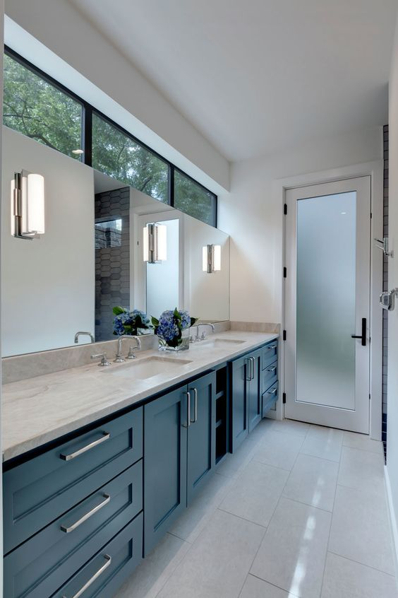a catchy blue farmhouse kitchen with white stone countertops, a large mirror and clerestory windows to natural light yet privacy