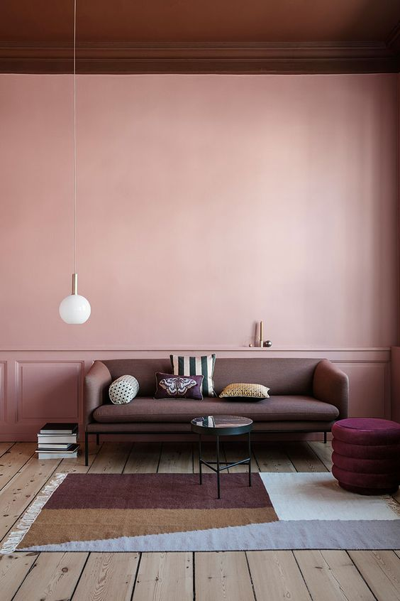 a catchy living room with a pink paneled accent wall, a dusty pink sofa, a purple pouf, a color block rug and a burgundy ceiling