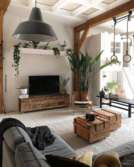 a catchy living room with industrial touches, with wooden beams and pillars, a grey sofa and a pendant lamp and some industrial wooden furniture items