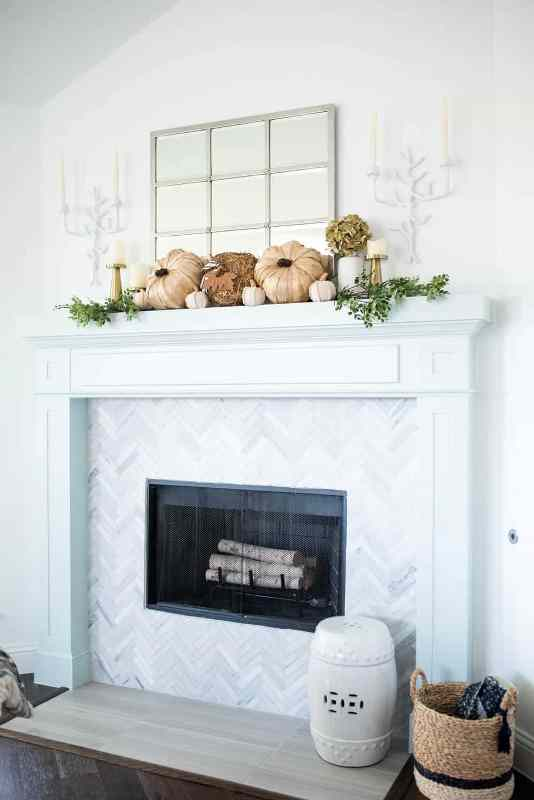 a catchy rustic mantel with faux pumpkins, greenery, dried blooms in a vase, gold candleholders with pillar candles, branch-inspired candleholders on the wall