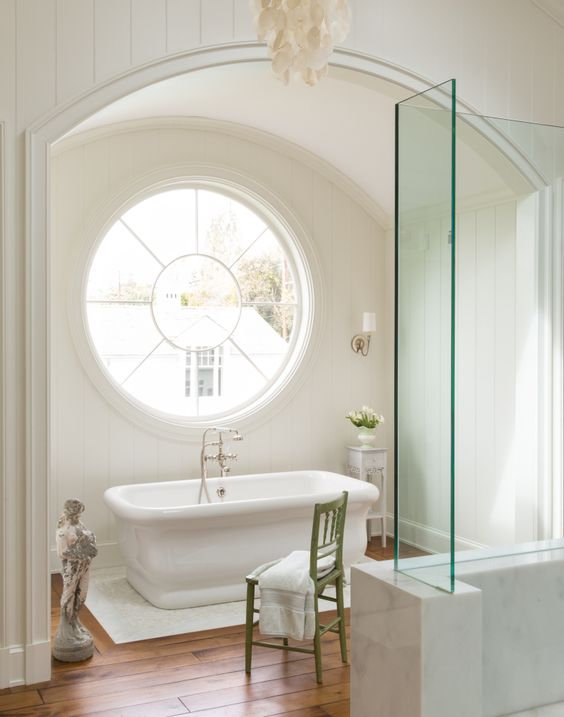 a chic and neutral bathroom is made catchier and more interesting with a porthole window over the bathtub