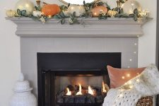 a chic fall mantel with neutral and orange pumpkins, greenery, candles and LED lights, a basket with pillows and a blanket plus lights