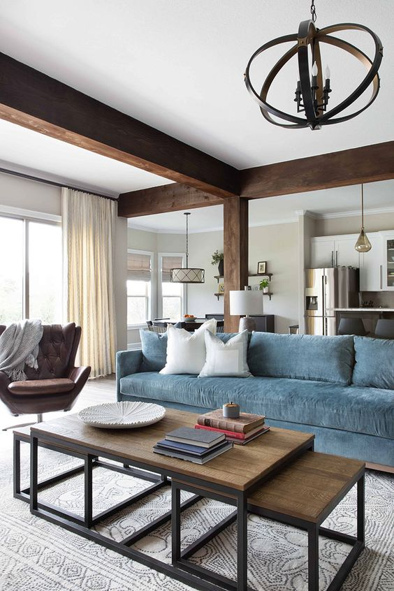 a chic living room with dark wooden beams and a pillar, a blue sofa, a brown leather chair and a duo of industrial coffee tables