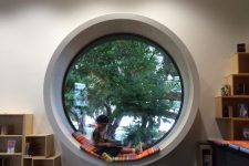 a chic staircase space done with storage boxes and a porthole window with a soft cushion to make up a seat
