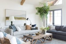 a coastal living room with wooden beams, a grey and a neutral sofa, a coffee table, woven chairs, blue and printed pillows and a potted tree
