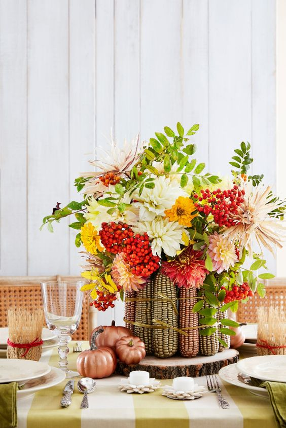a colorful Thanksgiving tablescape with a wood slice, corn cobs with bright blooms and berries, a striped tablecloth and green napkins