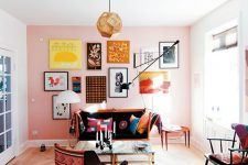 a colorful living room with a pink accent wall, a bold and cool gallery wall on it, an orange sofa with bright pillows, a burgundy chair and a faceted pendant lamp