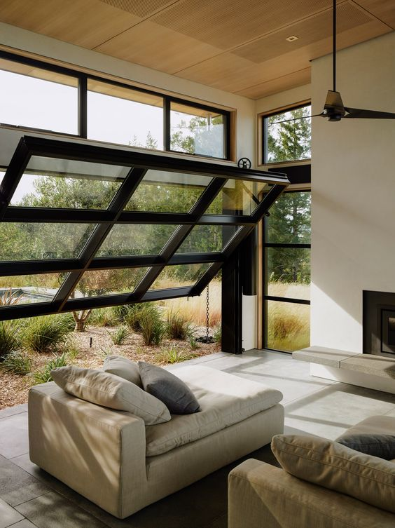 a contemporary all-neutral living room with a black framed garage door and views of the garden is a lovely idea for outdoor-indoor living