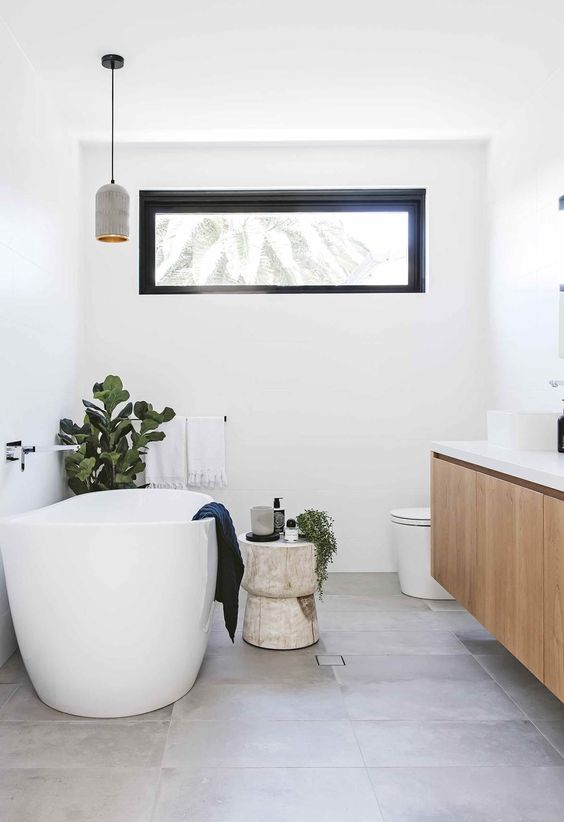 a contemporary bathroom with a floating vanity, an oval tub, a pendant lamp and a clerestory window that keeps privacy at its best