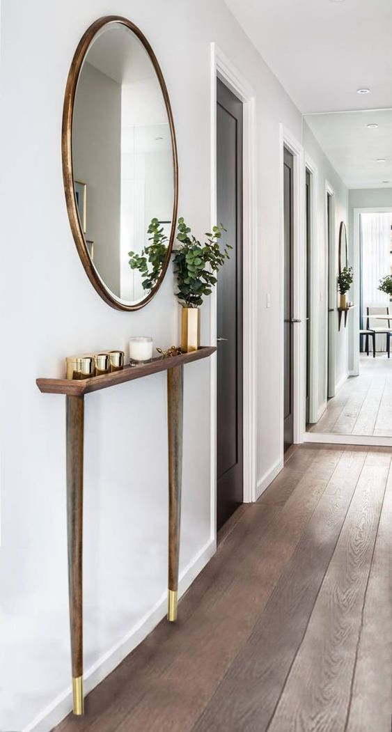 a contemporary entryway with a super sleek console with brass legs, brass jar candles and a vase, a round mirror in a brass frame is cool