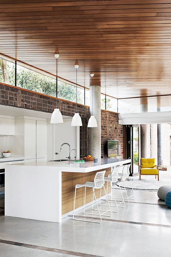 a contemporary space with a brick wall, white sleek cabinetry, pendant lamps and clerestory windows that birng light in