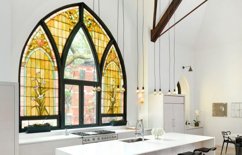 a contemporary to minimalist kitchen done in white, with wooden beams and bulbs hanging and a unique Gothic-style window with stained glass