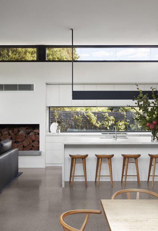 a contemporary white space with a long window as a backsplash and clerestory windows plus contemporary furniture