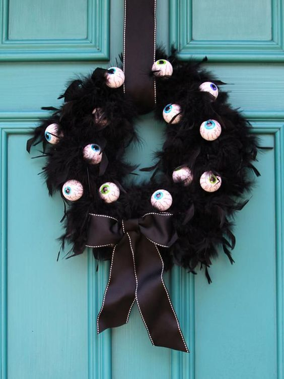 a cool and easy to DIY Halloween wreath of black feathers, scary eyes and elegant black ribbon is gorgeous and amazing