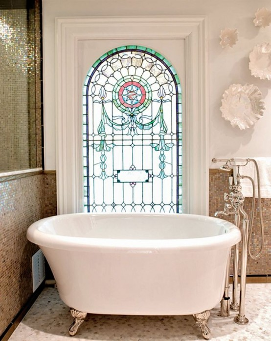 a cool bathroom with tan tiles and white walls, an oval tub on clawfoot legs and a stained glass window is a stylish space
